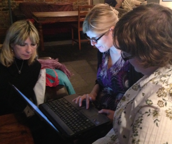Photo of Alison, Mel and Becky huddled around a laptop