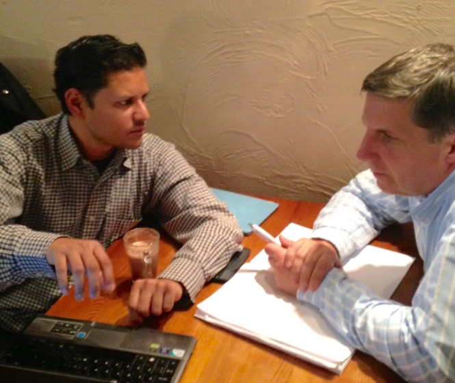 Photo of Deepak talking to John. Deepak has a laptop and coffee, John has a notepad and pen.