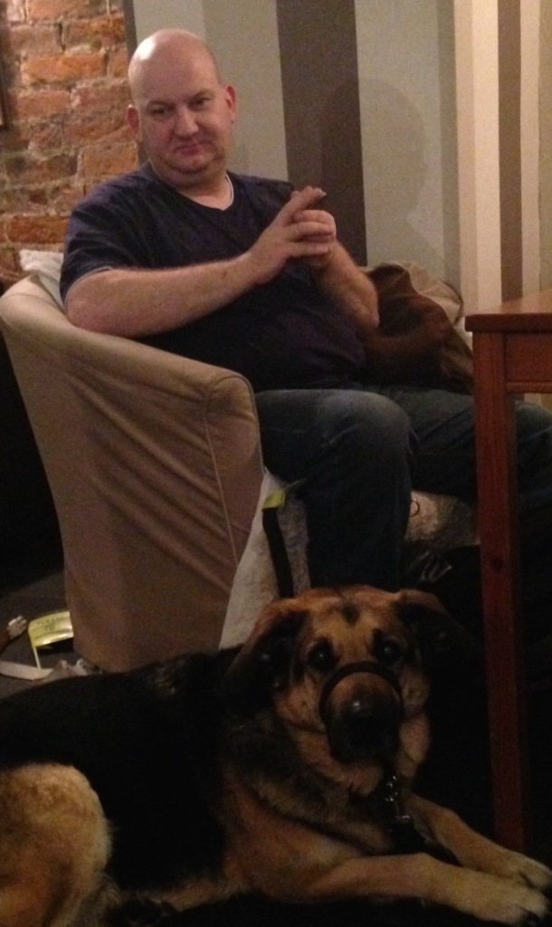 Karl sitting in a comfy chair by a cafe table with guide dog Quasi at his feet