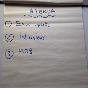 Flipchart with heading 'Agenda' and list 1. Exec update, 2. Interviews, 3. AOB