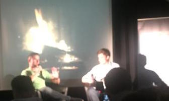 Photo of Joel Gascoigne and Nick Holzherr in front of screen with glowing fireplace